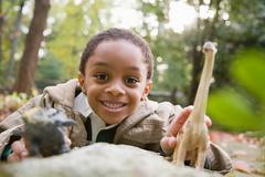 Boy with toy dinosaurs - stock photo