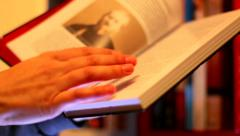 Man chooses a book in the library slider shoot RR Stock Footage