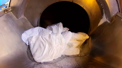 Dirty laundry enter in the tunnel washer system in the factory Stock Footage