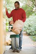 Father and son with groceries - stock photo