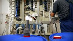 Worker controls the operation of industrial machine at factory - slider shoot Stock Footage