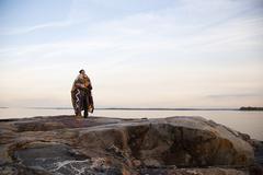 Mature couple hugging on rocks - stock photo