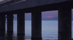 Sunrise under a bridge with concrete columns and a calm sea Stock Footage