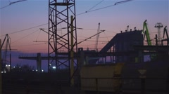 The locomotive , electric poles and cranes  as silhouettes before sunrise Stock Footage