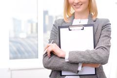 Confident businesswoman holding folder - stock photo