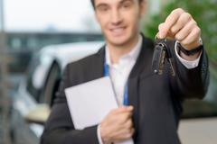 Young salesman is upholding the car keys - stock photo