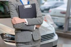 Saleswoman with clipboard is standing beside the car - stock photo