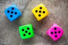 Stock Photo of Four color dices on canvas background