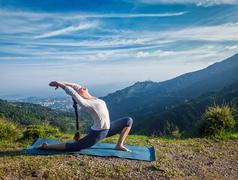 Woman practices yoga asana Anjaneyasana outdoors - stock photo