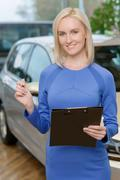 Attractive woman holding a clipboard - stock photo