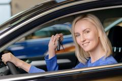 Pretty woman sitting inside her brand new vehicle Stock Photos