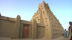 Mali Timbuktu Woman Walking in front of Mosque SlowMo Stock Footage