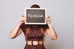 Young woman holding a chalkboard saying passion Stock Photos