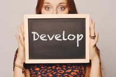 Young woman holding a chalkboard saying develop Stock Photos