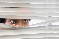 Woman looking through blinds Stock Photos
