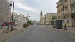 Walking and riding bikes on Krakowskie Przedmiescie on a cloudy day in Warsaw Stock Footage