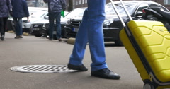Man Rolling Yellow Trolley Bag Stock Footage