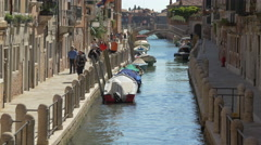 Tourists walking on a nice canal with bridges in Venice - stock footage