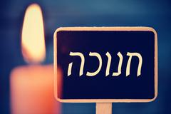 Candle and chalkboard with the text Hanukkah in Hebrew Stock Photos