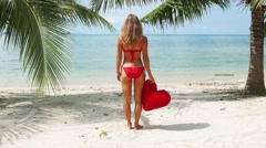 Woman in red bikini staying on the beach at the sea.  Stock Footage