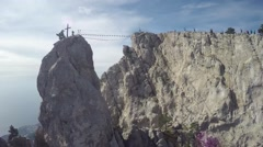 Aerial view of Cross Ai Petri Mountain, man walking on the suspension bridge Stock Footage