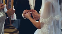 Hands of bride and groom exchanging wedding rings during christian wedding cerem Stock Footage