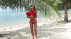 Gorgeous lady in red bikini staying on the beach at the sea. Stock Footage