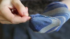 A woman sews up holes in socks Stock Footage