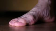 A woman wears holey socks Stock Footage