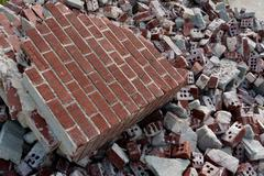 Broken Red Bricks Are Piled High At Demolition Site - stock photo