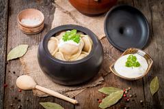 Meat Dumplings - russian pelmeni with sour cream - stock photo