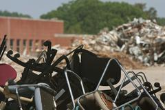 Piles Of Discarded Office Chairs And Debris At Demolition Site - stock photo