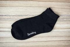 Trendy wool socks with inscription SUNDAY - stock photo