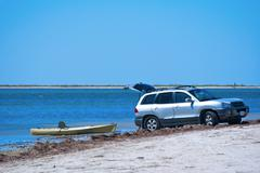 Launching a kayak from SUV Truck at beach Stock Photos