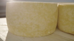 Round cheese matures in the cellar for deoevyaniy board. Close-up Stock Footage