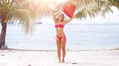 Lady in red bikini staying on the beach at the sea. Stock Footage