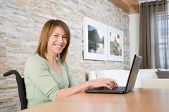 Disabled woman telecommuting - stock photo