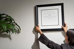 Business woman hanging framed certificate Stock Photos