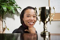 Business woman admiring her trophy - stock photo