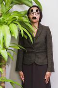 Businesswoman hiding behind plant wearing disguise - stock photo