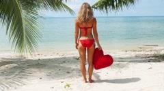 woman in red bikini standing on the beach  Stock Footage
