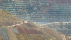 Mining trucks driving in huge copper mine - telephoto shot Stock Footage