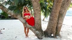 Beautiful woman in red bikini staying on the beach at the sea. Young cute teen Stock Footage