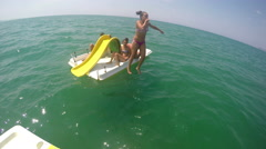 Pedal boat with people and girl jumping in the water Stock Footage