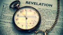 Pocket watch on Bible in Revelation with cross in it Stock Footage