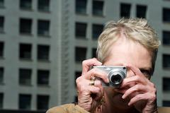 Woman taking a photograph Stock Photos