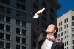 Stock Photo of Businessman looking up at sunlight