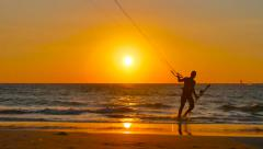 Kite Surfing  Man comes out of the sea at sunset. - stock footage