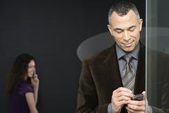 Woman with cellphone and man with handheld computer Stock Photos