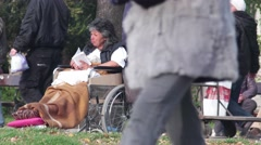 Stock Video Footage of A disabled woman sitting in a wheelchair at the park reading a book0
